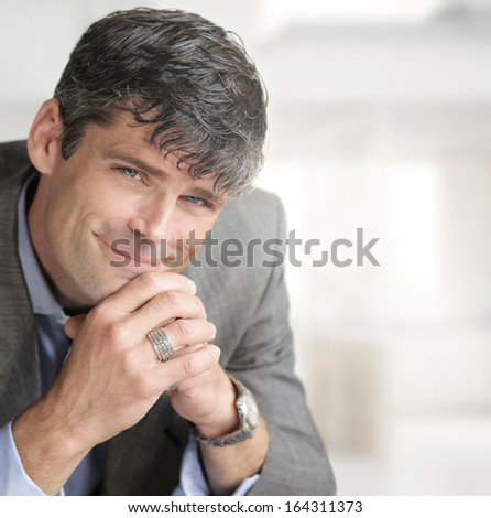 Portrait of a happy relaxed businessman in modern office setting - stock photo