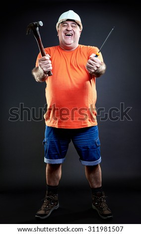 Portrait of a happy repairman wearing safety equipment holding hammer and screwdriver. Industry equipment concept. Full length. - stock photo