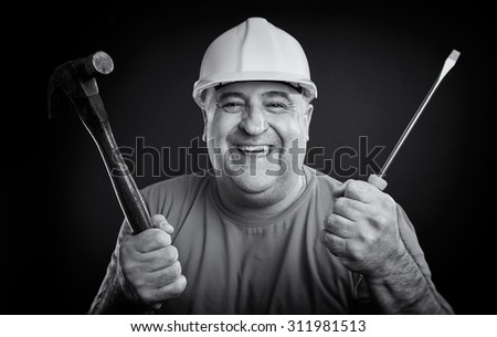 Portrait of a happy repairman wearing safety equipment holding hammer and screwdriver. Industry equipment concept. Black & white picture. - stock photo