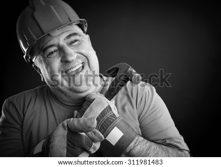 Portrait of a happy repairman wearing safety equipment holding hammer. Sepia picture. - stock photo