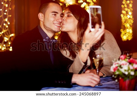 Portrait of a happy romantic couple making selfie photo with smart phone, cheerful girlfriend kissing her boyfriend on the cheek while taking self portrait - stock photo