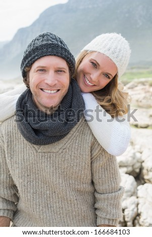 Portrait of a happy romantic young couple standing together on a rocky landscape - stock photo