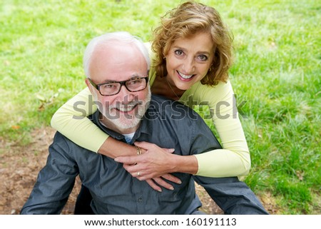 Portrait of a happy senior caucasian couple smiling outdoors - stock photo
