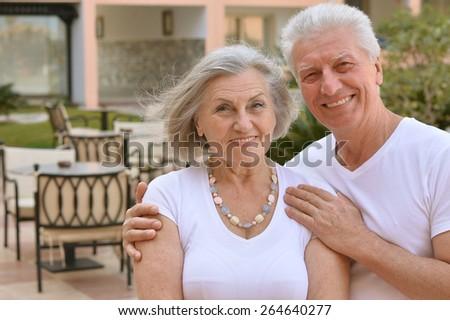 Portrait of a happy senior couple at tropic hotel resort - stock photo