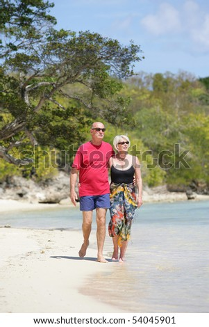 Portrait of a happy senior couple having a walk on the beach - stock photo