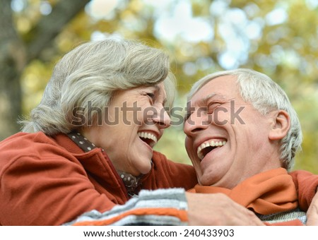 Portrait of a happy senior couple in autumn park - stock photo