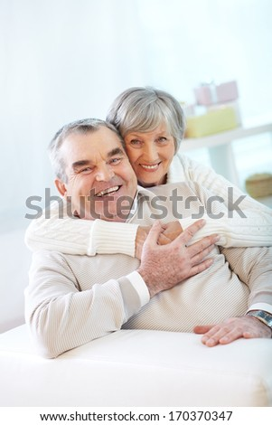 Portrait of a happy senior couple looking at camera - stock photo