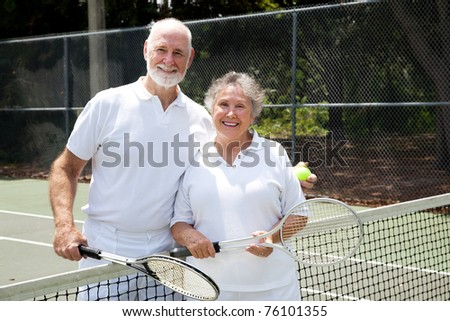 Portrait of a happy senior couple on the tennis courts. - stock photo