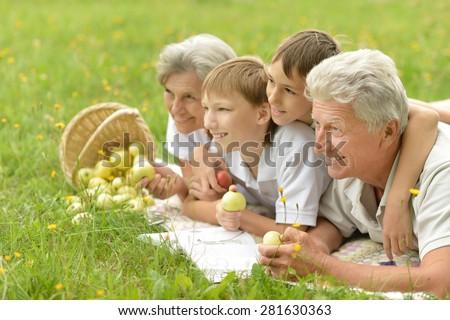 Portrait of a happy senior couple with grandchildren - stock photo