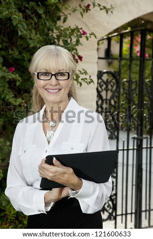Portrait of a happy senior female agent with clipboard - stock photo
