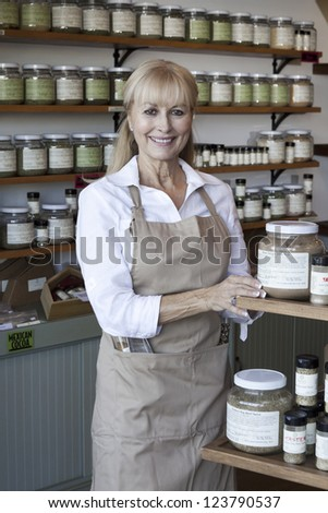 Portrait of a happy senior female employee in spice store - stock photo
