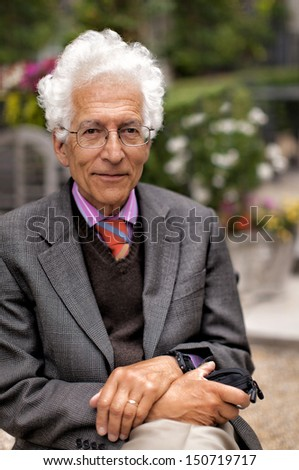 Portrait of a happy senior man with white hair wearing a pink shirt with a tie and jacket, sitting outside in a garden. Shot with shallow dof. - stock photo