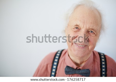Portrait of a happy senior well-dressed man looking at camera - stock photo
