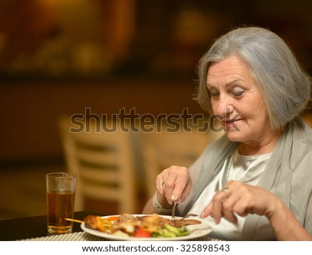 Portrait of a happy senior woman eating breakfast at cafe - stock photo