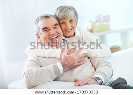 Portrait of a happy senior woman embracing her husband and both looking at camera - stock photo