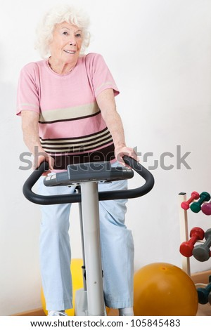 Portrait of a happy senior woman exercising on bike in gym - stock photo