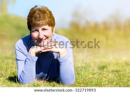 Portrait of a happy senior woman on field. - stock photo