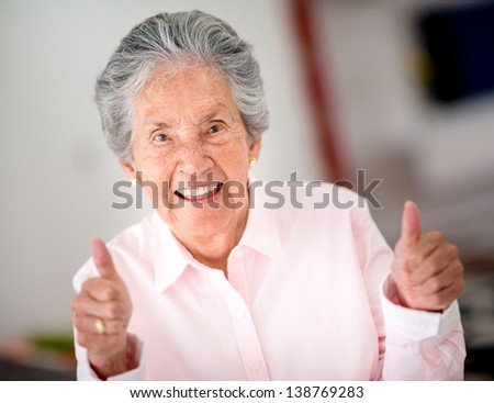 Portrait of a happy senior woman with thumbs up - stock photo
