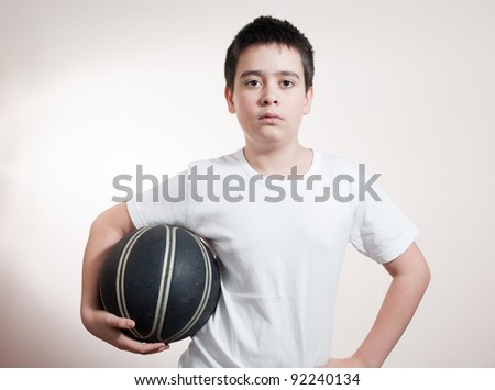 Portrait of a happy small boy holding basket ball isolated over white background - stock photo