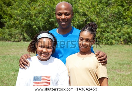 Portrait of a happy, smiling African-american family - father, mother, and daughter.  The mother has cerebral palsy. - stock photo