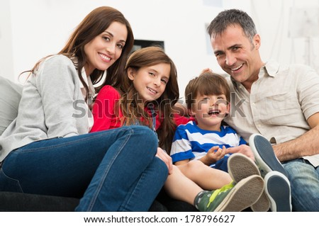 Portrait Of A Happy Smiling Family Sitting On Couch - stock photo