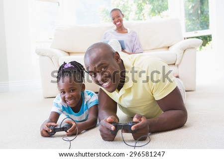 Portrait of a happy smiling father playing with her daughter at video games in living room - stock photo