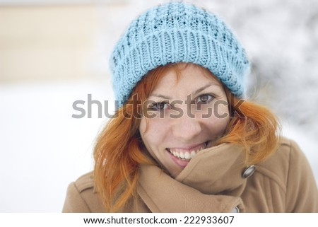 Portrait of a Happy smiling young woman in the winter scenery - stock photo