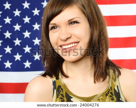 portrait of a happy smiling young woman standing near the American flag - stock photo