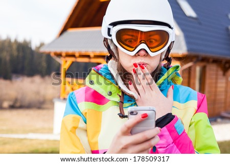 Portrait of a happy snowboarder in the helmet and ski goggle with mobile phone. - stock photo