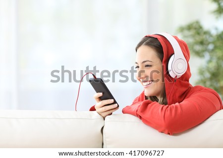 Portrait of a happy teen listening music on line from smart phone sitting in a couch at home with white curtains in the background - stock photo