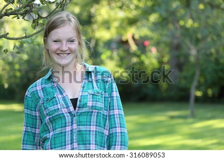 Portrait of a happy teenage girl in the garden - stock photo