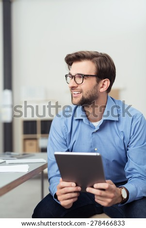 Portrait of a Happy Thoughtful Office Man Holding a Tablet Computer While Sitting at his Office and Looking to the Left of the Frame. - stock photo