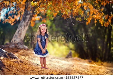 portrait of a happy toddler girl at beautiful autumn park  - stock photo