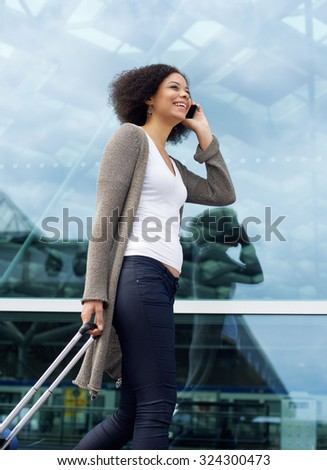 Portrait of a happy travel woman walking with mobile phone and suitcase - stock photo