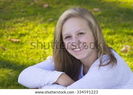 Portrait of a happy twelve year old girl on the grass. - stock photo