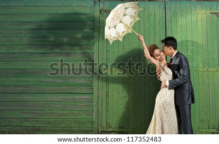 Portrait of a happy wedding couple outdoors. Groom kissing bride - stock photo