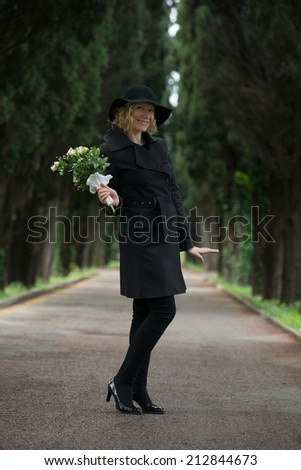 Portrait of a happy woman at cemetery - stock photo