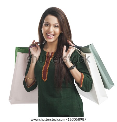 Portrait of a happy woman carrying shopping bags - stock photo
