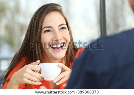 Portrait of a happy woman dating with perfect smile and white teeth in a snack bar interior with a window and outdoors in the background - stock photo