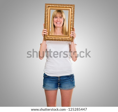 Portrait Of A Happy Woman Holding Frame against a grey background - stock photo