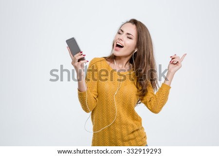Portrait of a happy woman listening music in headphones isolated on a white background - stock photo