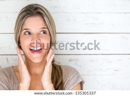 Portrait of a happy woman looking very surprised - stock photo