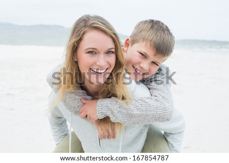 Portrait of a happy woman piggybacking her cheerful son at the beach - stock photo