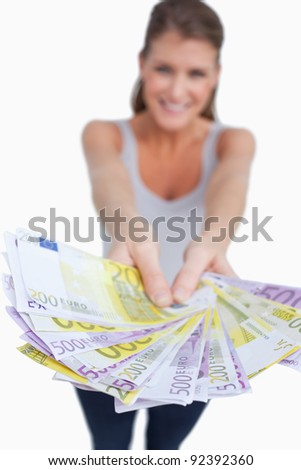 Portrait of a happy woman showing bank notes against a white background - stock photo