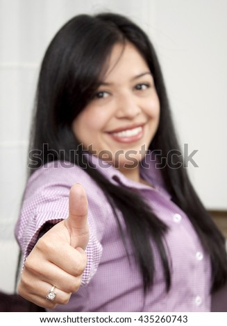 Portrait of a happy woman showing thumbs up  - stock photo