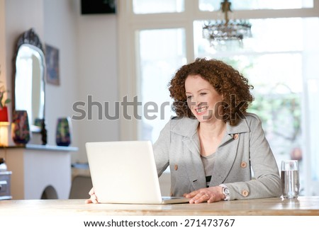 Portrait of a happy woman sitting at table at home looking at laptop - stock photo