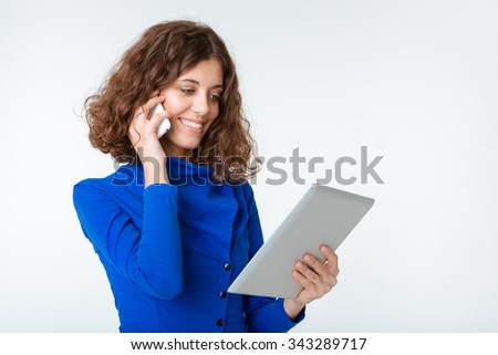 Portrait of a happy woman talking on the phone and using tablet computer isolated on a white background - stock photo