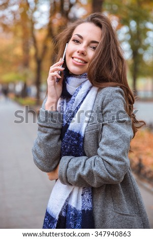 Portrait of a happy woman talking on the phone outdoors  - stock photo