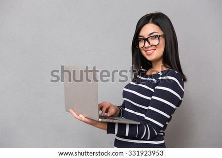 Portrait of a happy woman using laptop computer over gray background and looking at camera - stock photo
