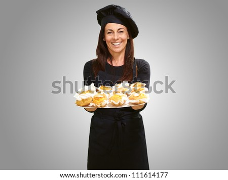 Portrait Of A Happy Woman While Holding Cupcake On Gray Background - stock photo